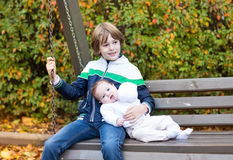 Little boy and his newborn baby sister on swing Stock Image
