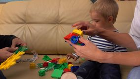 Little boy and his parents playing with construction set at home together. 4K shot stock video