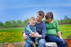 Little boy with his parents sitting on a tree stump Stock Photography