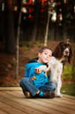 Little boy with his pet dog. Young child with his pet dog outdoors in the fall Royalty Free Stock Photo