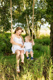 A little boy with his pregnant mother sitting on a swing. Pregnant mom with a boy resting in a meadow. Mother and son outdoors in summer Royalty Free Stock Photo