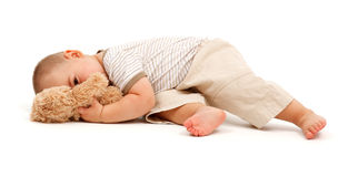 Little boy with his toy bear. Tired little boy peeking from behinde toy bear Stock Image