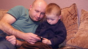Little boy with his uncle watching a movie on phone stock video footage
