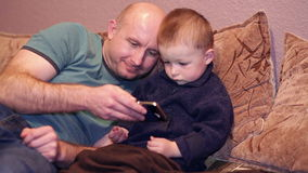 Little boy with his uncle watching a movie on phone stock video