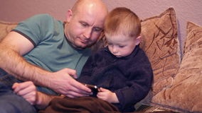 Little boy with his uncle watching a movie on phone stock footage