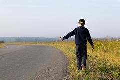 The little boy hitchhiking. A boy in a dark sweatshirt hitchhiking on a field road on a clear summer day Stock Image