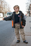 Little boy hitchhiking on the road Royalty Free Stock Photo