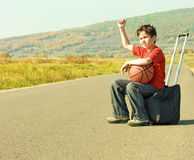 Little boy hitching on road. A boy hitchhikes on the side of the road stock image