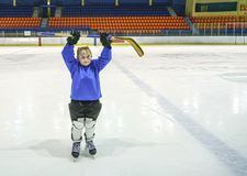 Little boy hockey player with full equipment and in blaue uniform on ice hockey rink. Sport for children. Little boy hockey player in blaue uniform posing with a royalty free stock photos