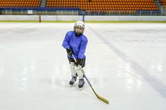 Little boy hockey player in blaue uniform posing with a hockey stick on ice hockey rink. Sport for children royalty free stock photography