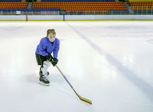 Little boy hockey player with full equipment posing with a hocke Royalty Free Stock Images