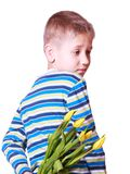 Little boy hold flowers behind back. Royalty Free Stock Photos