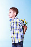 Little boy hold flowers behind back. Stock Photo