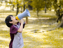 Little boy hold megaphone shouting in the park Stock Photo