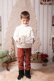 Little boy hold present in Christmas interior Stock Images