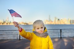 Little boy holding the American flag on the background skyscrapers of Manhattan stock photos
