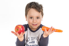Little boy holding an apple and a carrot. Stock Photo