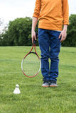 Little boy holding badminton racquet and standing on green grass with shuttlecock near by. Cropped shot of little boy holding badminton racquet and standing on royalty free stock image