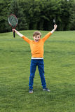 Little boy holding badminton racquet and triumphing while standing on grass. Cheerful little boy holding badminton racquet and triumphing while standing on grass stock photos