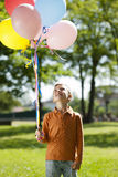 Little boy holding balloons. Outdoors Royalty Free Stock Photography