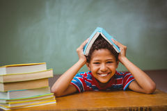 Little boy holding book over head in classroom Stock Images