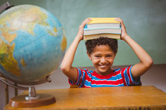 Little boy holding books over head in classroom Stock Photo