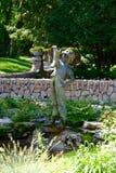 Little Boy holding a boot fountain, Assiniboine Park, Winnipeg, Manitoba, Canada. Leo Mol statue Little Boy holding a boot fountain, Assiniboine Park, Winnipeg stock images