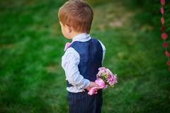Little boy holding a bouquet of flowers behind his back Stock Photography
