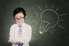Little boy holding bright light bulb Stock Photo