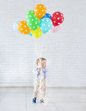 Little boy holding a bunch of colored balloons Royalty Free Stock Photography