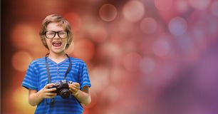 Little boy holding camera while laughing Stock Images