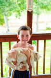 Little Boy Holding Cat. Cute little boy with no shirt in the summer carrying a cat in his arms Stock Photo