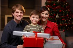 Little boy holding christmas presents. Portrait of little boy and happy parents holding christmas presents, smiling Royalty Free Stock Photography