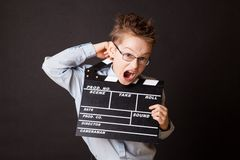 Little boy holding clapper board in hands. Royalty Free Stock Photography