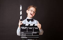 Little boy holding clapper board in hands. Royalty Free Stock Photos