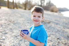 Little boy holding clean water in dotted mug Stock Photo