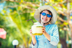 Little boy holding coconut cocktail on tropical beach resort stock images