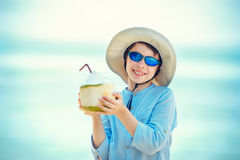 Little boy holding coconut cocktail on tropical beach resort royalty free stock photography