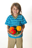 Little boy holding colorful peppers Royalty Free Stock Image