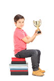 Little boy holding a cup seated on stack of books Royalty Free Stock Photos