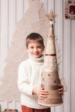 Little boy holding decorated Christmas tree in Christmas interio Royalty Free Stock Photos