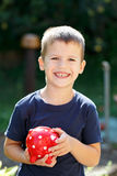 Little boy holding dotted piggy bank outdoor Stock Images