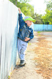 Little boy holding on fence outdoors Stock Images