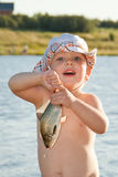 Little boy holding a fish. Little boy in panama hat holding a fish is on the bank of a pond Stock Images