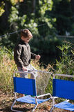 Little boy holding fishing net by chairs. On sunny day Royalty Free Stock Photos