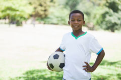 Little boy holding football in the park smiling at camera Stock Photo