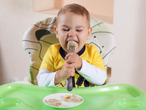 The little boy is holding a fork and eats itself. Portrait of the kid who eats itself Royalty Free Stock Image