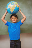 Little boy holding globe over head Royalty Free Stock Image