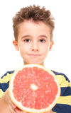 Little boy holding grapefruit Stock Photos