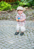Little Boy Holding Handfuls of Colorful Easter Eggs Stock Photo